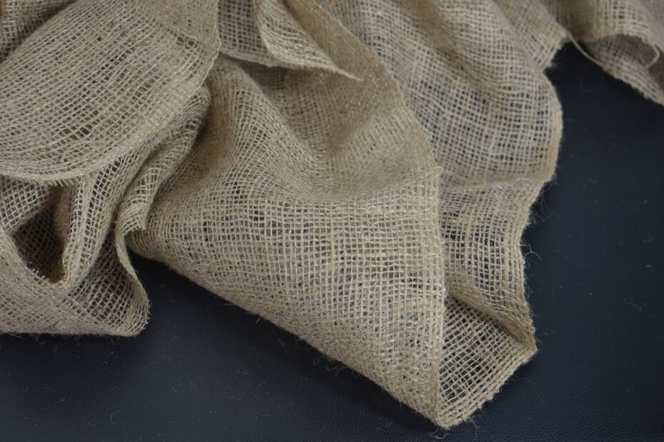 creased eco sackcloth with holes on black background
