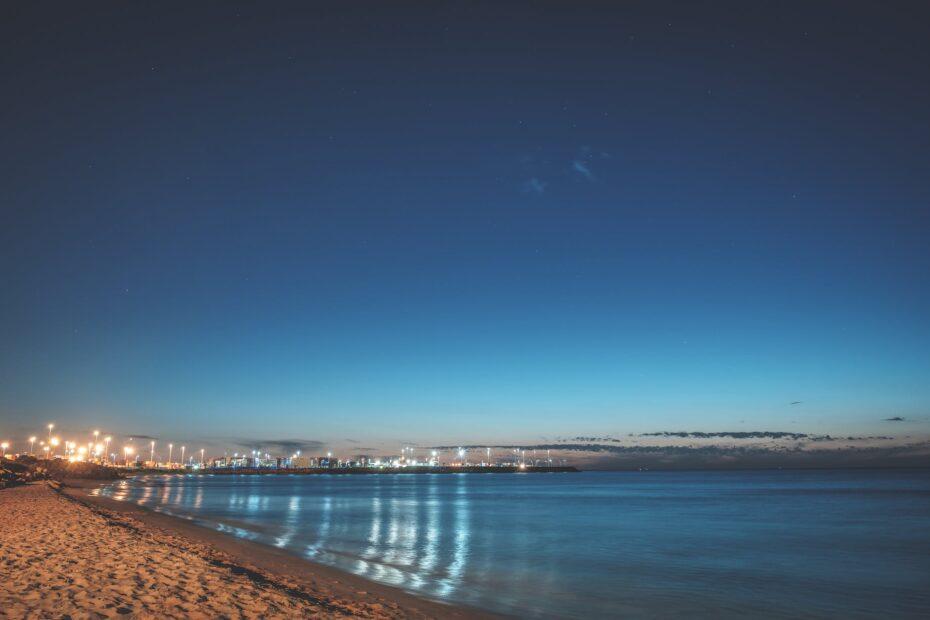 sandy embankment of river with luminous streetlights