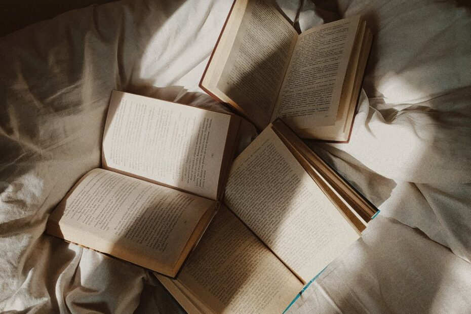 opened books placed on disheveled bed