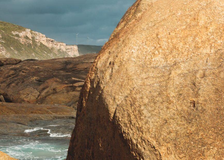 rocky coast near azure sea under cloudy sky