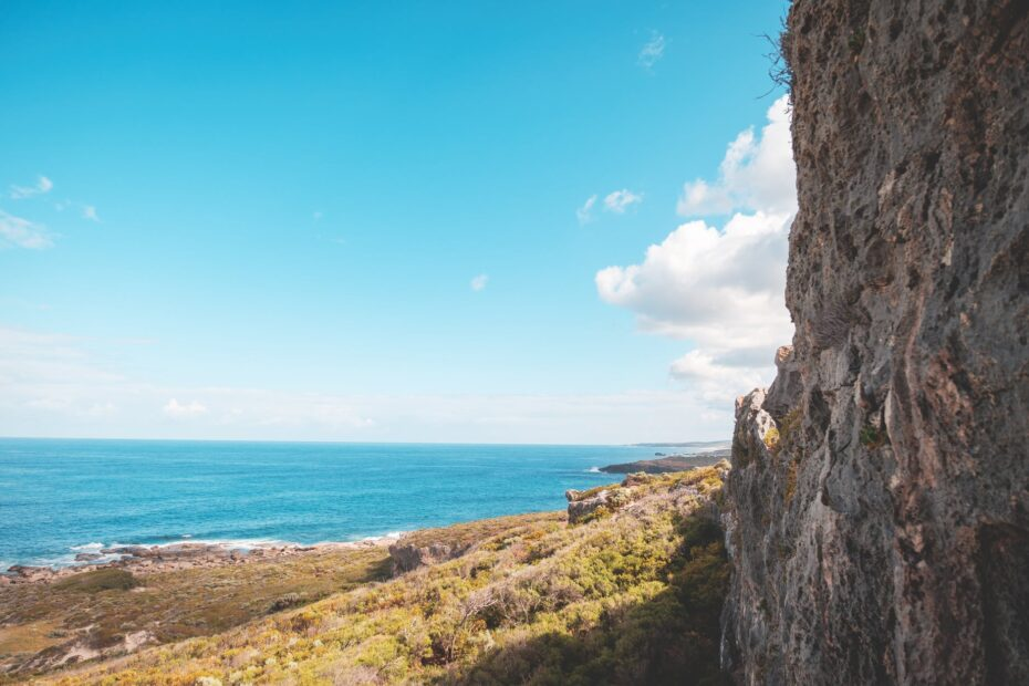 shore with rocky cliff under cloudy blue sky