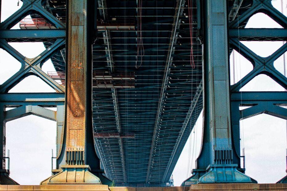 blue metal bridge in low angle photo at daytime