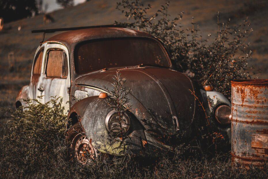 photo of abandoned vintage volkswagen beetle near rusty drum