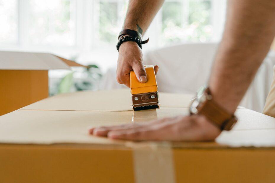 crop man packing carton box with scotch tape dispenser